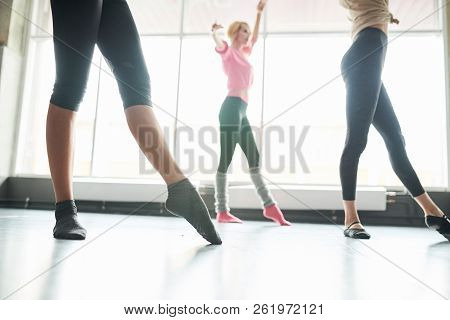Side View Low Section Of Group Of Unrecognizable Young Women Practicing Ballet Moves In Sunlit Dance