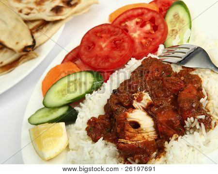a plate of chicken tikka masala, served with white rice, a side salad and flat chapatti or naan bread.