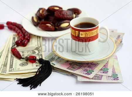 Coffee, dates stuffed with almonds and worry beads, on piles of Qatari Arab money and US dollars. Sweet food and coffee are inevitable accompaniments to any business dealings in the arab world