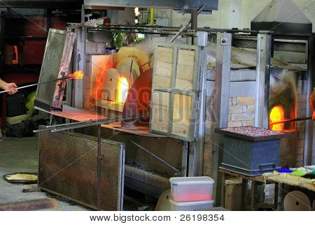 Decorative glass being manufactured at Murano, Venice, Italy. A glassma\ker is removing a blob of molten glass on a the end blowpipe from the furnace