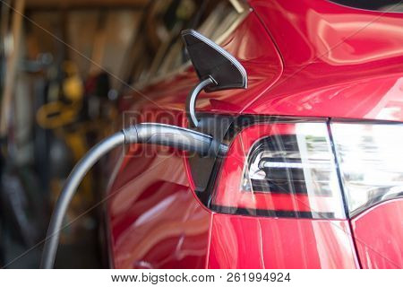 Red Electric Vehicle Plugged In Garage