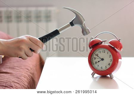 Sleepy Woman In The Bed Is Trying To Smash A Red Alarm Clock By Hammer In Her Hand. Kill The Alarm C