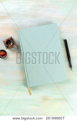An Overhead Photo Of An Ink Well With A Teal Journal, With A Nib Pen, On A Blue Background With Copy