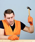 Carpenter, woodworker on concentrated face hammering nail into wooden board. Handcrafting concept. Man, handyman in bright vest and protective gloves handcrafting, light blue background poster