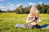 Young female with open arms and long blond hair sitting back and relaxes in yoga pose in green nature poster