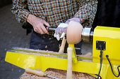 unrecognizable craftsman turning wood with lathe, woodworking craftsmanship poster