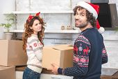 happy young couple unpacking cardboard boxes during relocation at christmastime poster