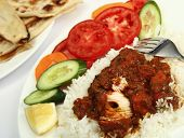 a plate of chicken tikka masala, served with white rice, a side salad and flat chapatti or naan bread. poster