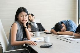 Bored Business People And Sleeping Resting On Workplace During Work Meeting, Concept Of Exhausted Bu