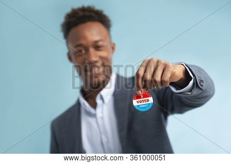 Close Up Of Patriotic Campaign Button In Hand Of African American Businessman Voter, Elections In Us