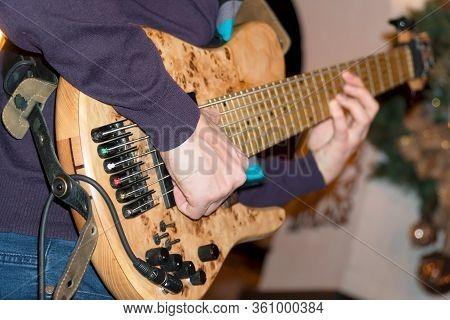 The Bass Player Plays A Five-string Bass Guitar Close-up. Plays Bass Guitar. Selective Focus