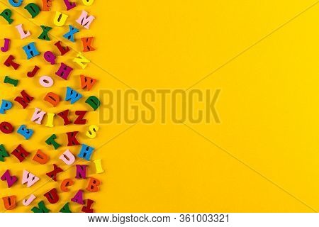 Multicolored Alphabet Background. Colorful Letters Of The English Alphabet Are Scattered On Yellow B