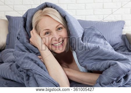 Happy Woman Hiding Under The Duvet In The Bed