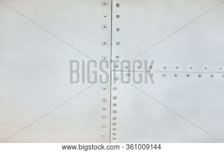 Silver Metal Surface Of The Aircraft Fuselage With Rivets. Fuselage Detail View. Airplane Metallic F
