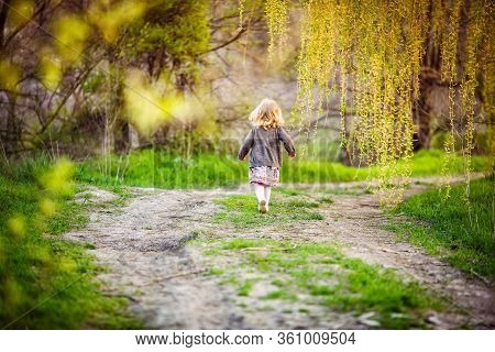 The Little Girl Ran Down The Path, Running Away From Parents In The Park. A Naughty Child. Spring La