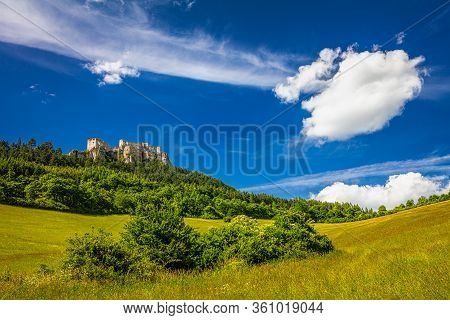 The Ruins Of A Medieval Castle Lietava On A Rocky Blade Over A Wooded Landscape And Grassy Meadows,