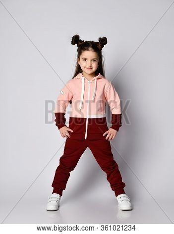 Frolic Smiling Kid Girl With Straight Brunette Hair With Buns In Two-colored Pink Brown Sport Suit H