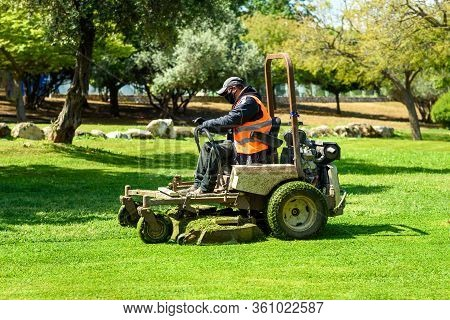 Man Wearing Black Face Mask Mows The Grass With Lawn Mower. Mow The Lawns.