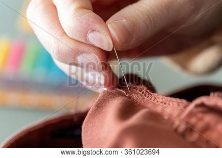 A Close Up Portrait Of A Hand Of Someone Holding A Needle, Sewing A Hole In A Pair Of Pants At The S