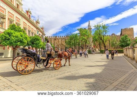 Seville, Andalusia, Spain - April 18, 2016: Tourists Making A Horse Carriage Ride In Triumph Square