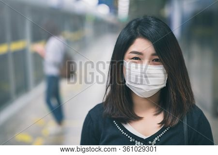 Young Asian Woman Wearing Protective Face Mask In Subway Due To The Polluted Air Or Pm 2.5 And Coron