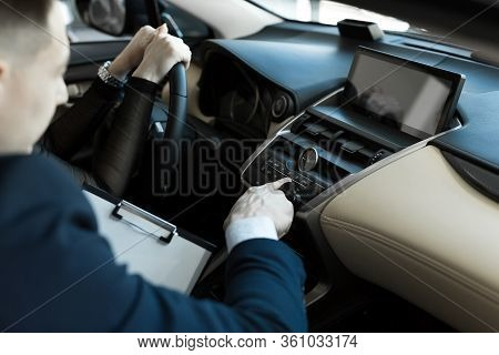Agent And Buyer Girl Inside A Car In A Car Dealership. The Seller Shows The Car To The Buyer
