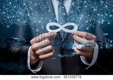 The Concept Of Unlimited Traffic On The Internet. Businessman Holds An Infinity Sign On A City Backg