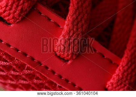 Close-up Of Bright Red Sneaker With Laces. Fashionable Designed Shoe And Handmade Production. Sport