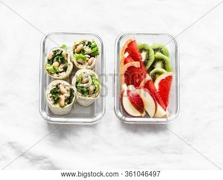 Healthy Food Lunch Box - Fresh Fruit And Chicken, Beans, Green Salad Pita Bread Wraps On A Light Bac