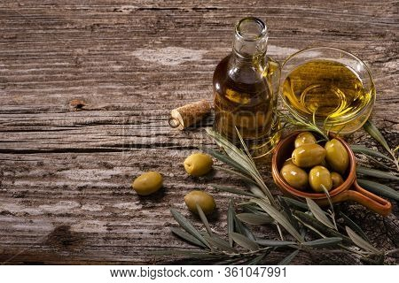 In The Foreground, On The Rustic Wooden Table, Bowls With Green Olives, Olive Branch And Extra Virgi