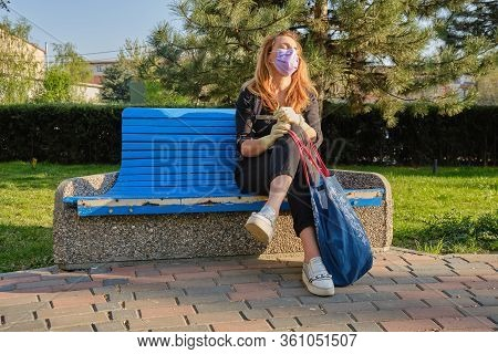 Woman With Medical Mask And Gloves Sits On A Bench And Takes A Short Break, Enjoys A Few Sun Rays, O