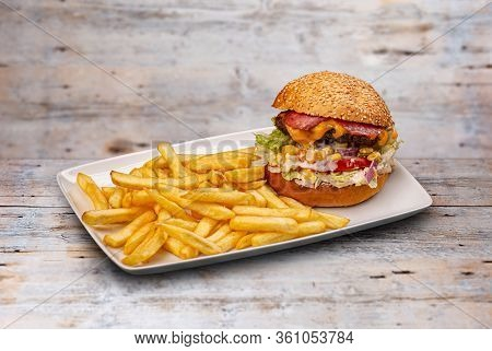 Big Burger With French Fries On Wooden Background