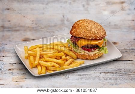 Hamburger And French Fries In White Plate On Wooden Table