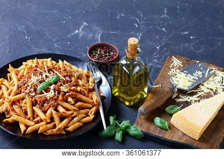 Wholewheat Pasta Penne Bolognese Topped With Shredded Parmesan And Basil On A Black Plate On A Concr