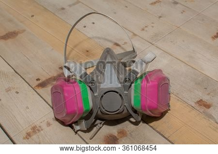 A Professional Respirator Mask Set Upon A Barn Wood Background.