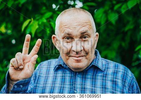 Aged Boomer Man Making Ok Peace Sign Over Green Park Background. Winner. Success. Positive Senior Sm