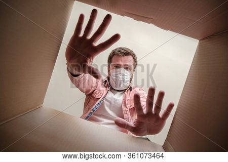 Frightened Man In A Medical Mask Unboxing Inside View A Delivered Box, Shows A Stop Gesture With Han
