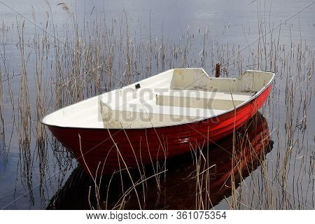 Red And White Plastic Rowing Boat Without Oars.