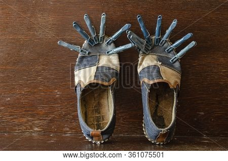 A Pair Of Frayed Shoes With Clothespins. Repair Old Shoes. Clothespins Hold The Glued Sole. Close-up