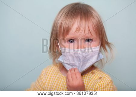A Little Girl In A Medical Mask Isolates On A Blue Background. The Concept Of Coronavirus, Quarantin