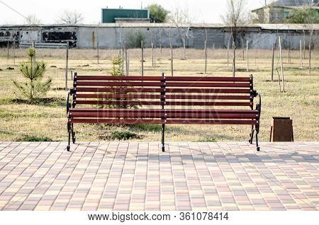 Bench In A City Park. Brown Bench Made Of Wood. A Place To Relax. Bench