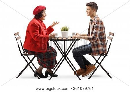 Full length profile shot of a young man and a senior woman sitting in a cafe and talking isolated on white background
