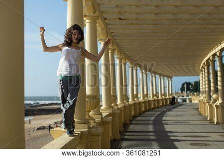 Beautiful asian woman walks along the railing of the ocean promenade.