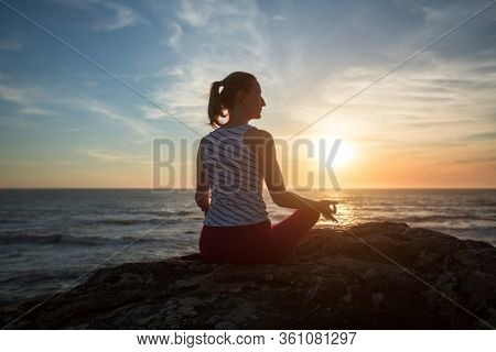Yoga woman meditation on the ocean beach at amazing sunset.