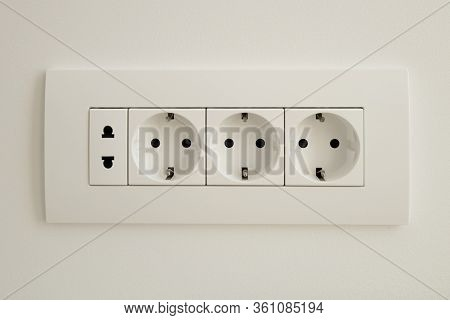 A Block Of White Outlets Consisting Of Three Eu Standard Outlets With Grounding And One Us Standard