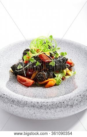 Chicken hearts in black tempura with vegetables. Roasted meat with cut tomatoes and garden cress closeup view. Asian cuisine, japanese recipe. Delicious restaurant dish served with greenery