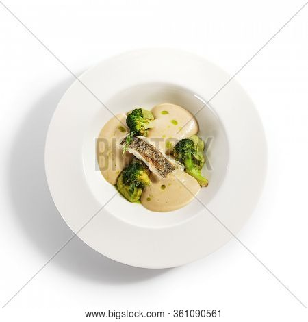 Sea cod fillet top view. Served cuisine. Dish with fish and baked broccoli puree ingredients in white plate isolated. Luxury culinary. Restaurant food portion, delicious supper, main course