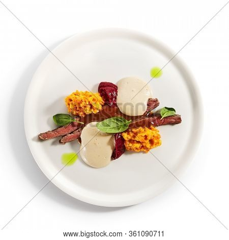 Duck breast with carob sauce and vegetables. Served roasted meat with carrot and pumpkin risotto in plate. Gourmet culinary, gastronomy. Restaurant food portion, cooked main course