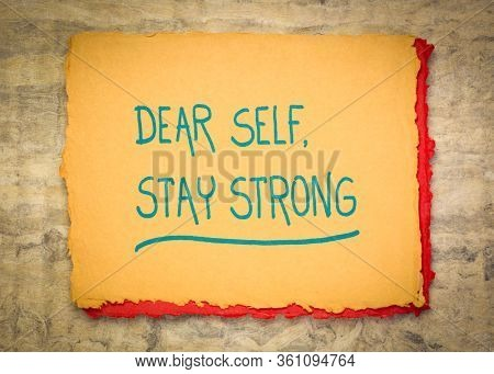 Dear self, stay strong - inspirational note. Handwriting on a rough handmade rag paper. Motivation concept.