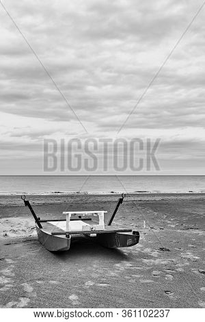 Safety boat - catamaran by the sea on empty beach in Rimini at off-season, Italy - Minimalistic landscape, black and white photography